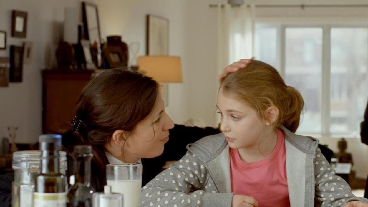 Une femme caresse la tête d'une petite fille à table
