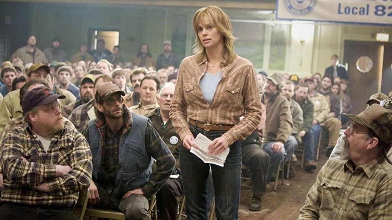 Une femme (Charlize Theron) en jeans et chemise carrottée, debout au milieu d'une assemblée d'hommes assis.