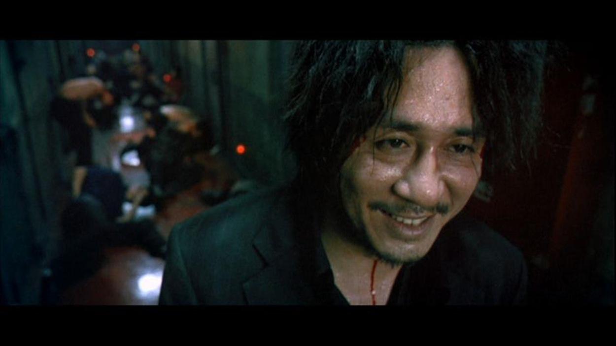 Un homme souriant et ensanglanté, devant un tas de corps dans un couloir