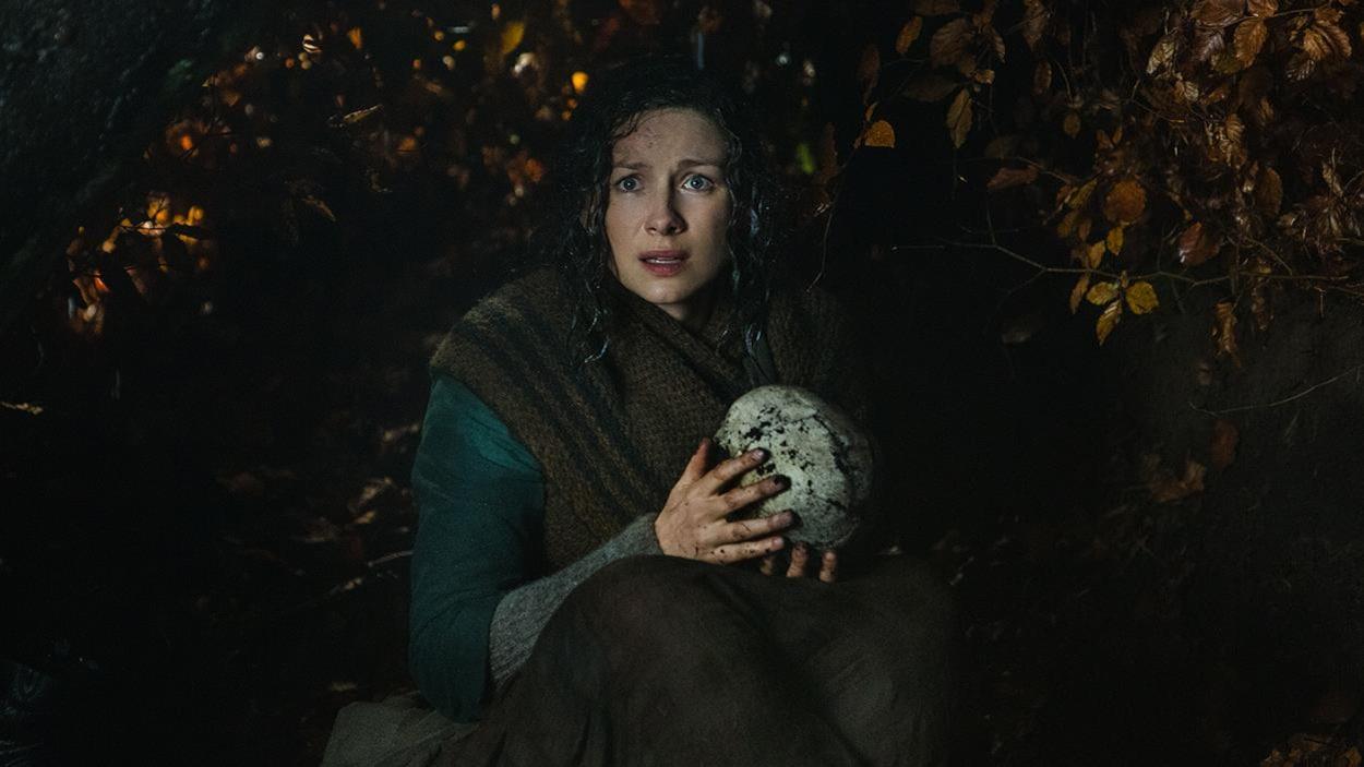 Claire cachée sous un arbre en forêt découvre un crâne et le prend dans ses mains.