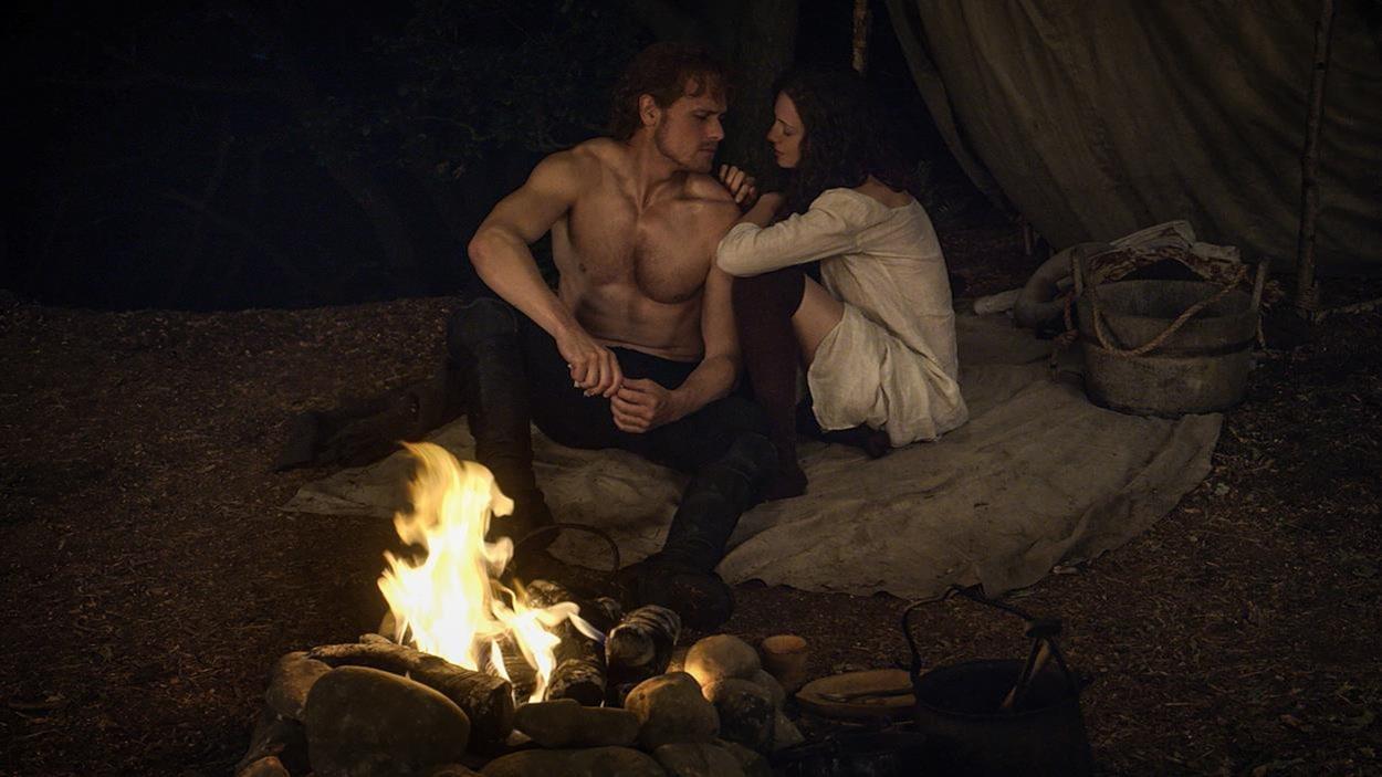 Jamie est torse nu et Claire est à ses côtés. Ils jasent collés près du feu.