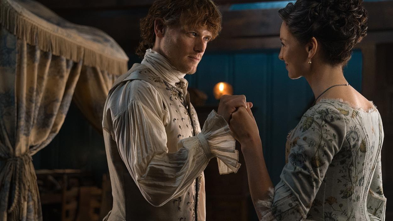 Jamie prend la main de Claire et ils se regardent amoureusement.
