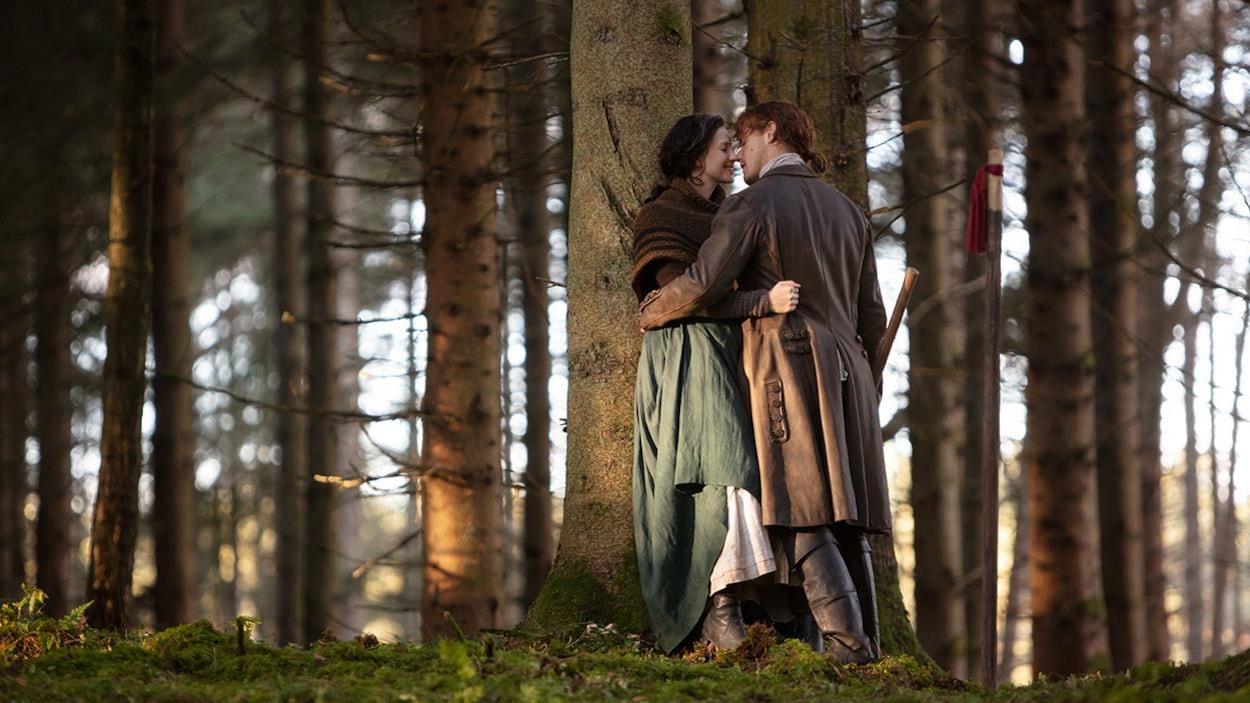 Claire et Jamie s'embrassent, appuyés contre un arbre.