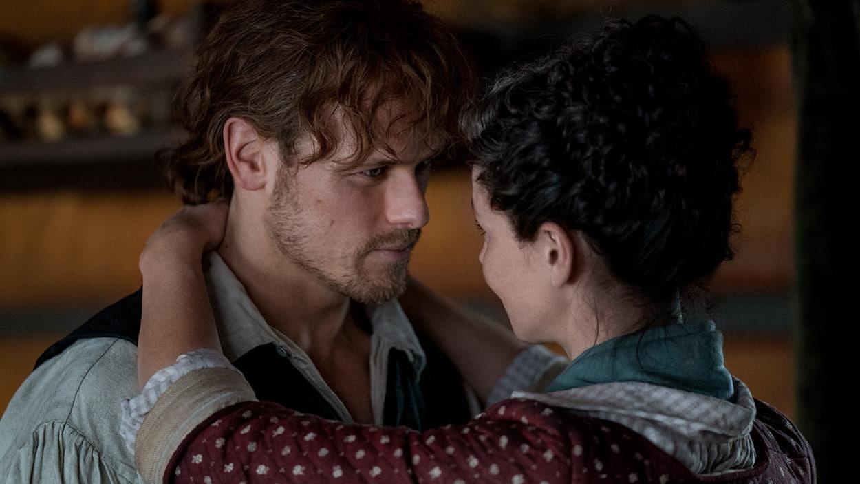 Claire a les bras autour du cou de Jamie et ils se regardent amoureusement.