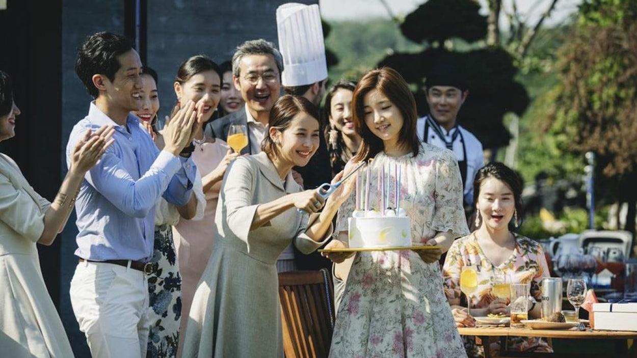 Dans un jardin, une femme coupe un gâteau tenue par une autre femme, au milieu d'une foule qui applaudit.