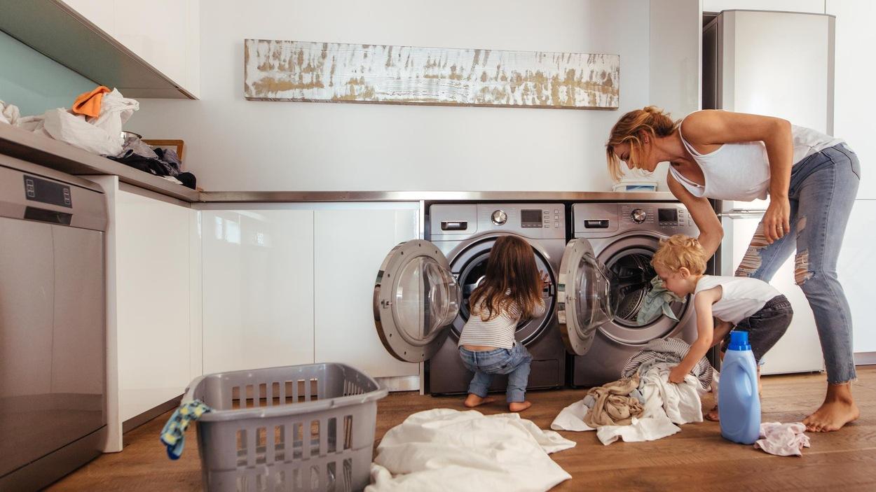 Une mère et ses deux enfants remplissent une laveuse de vêtements.