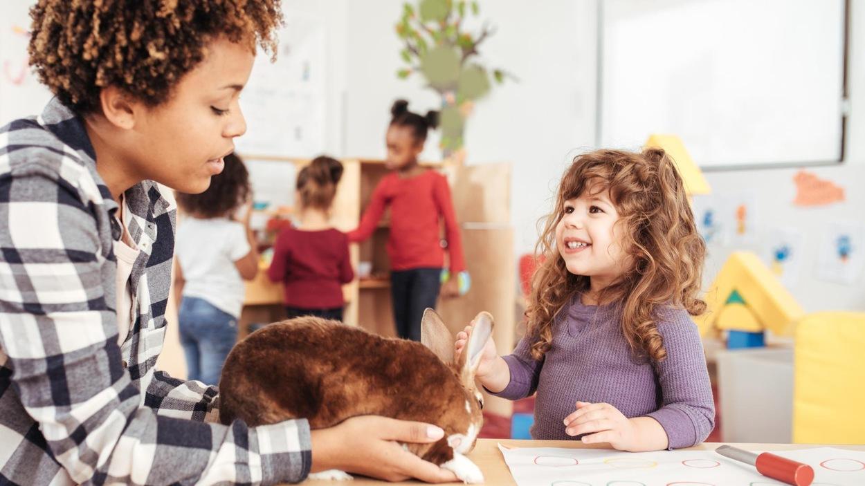 Une professeure et une élève s'amusent avec un lapin dans une salle de classe.