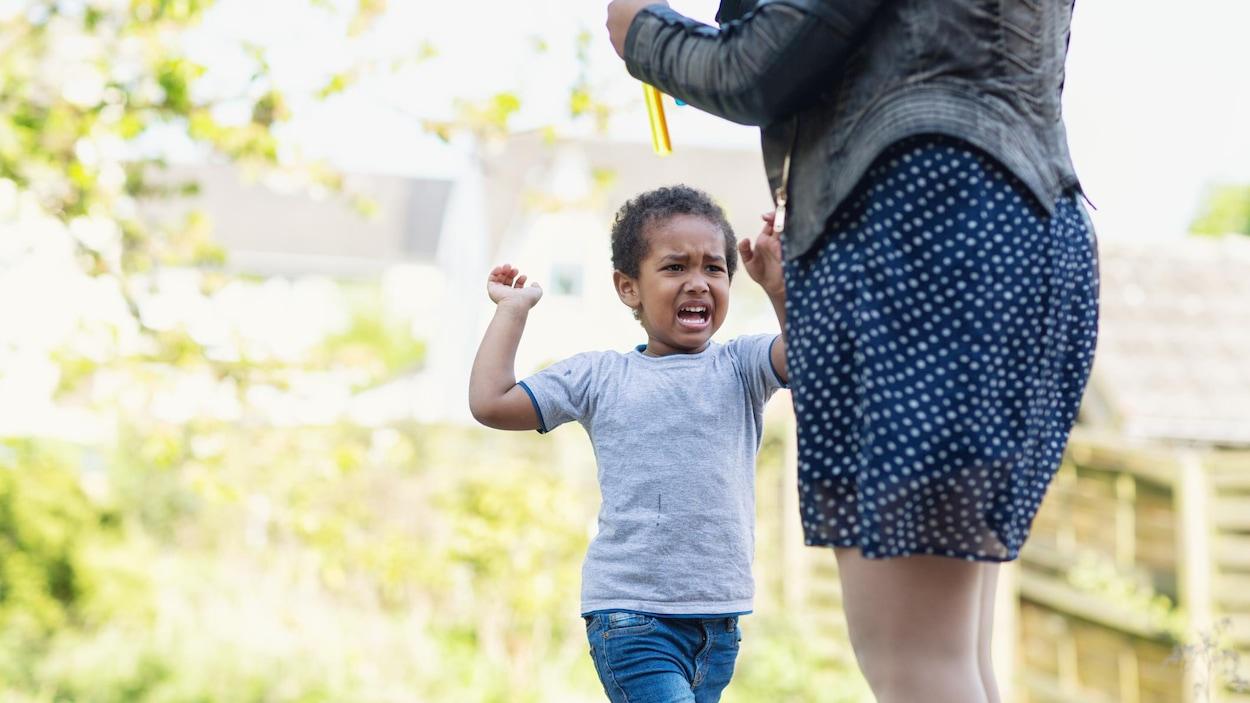 Un petit garçon en colère fait mine de vouloir frapper sa mère.