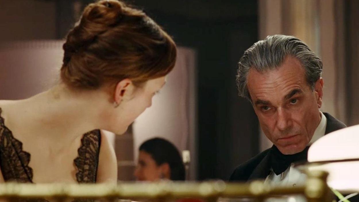 Un homme aux cheveux gris, l'air sévère, regardé par une femme en robe, de dos