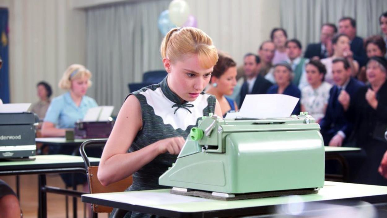 Une jeune fille penchée sur sa machine à écrire verte oâle, durant un concours de dactylographie