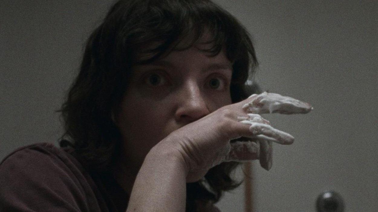 Une jeune femme (Larissa Corriveau), l'air effaré, la main devant la bouche.