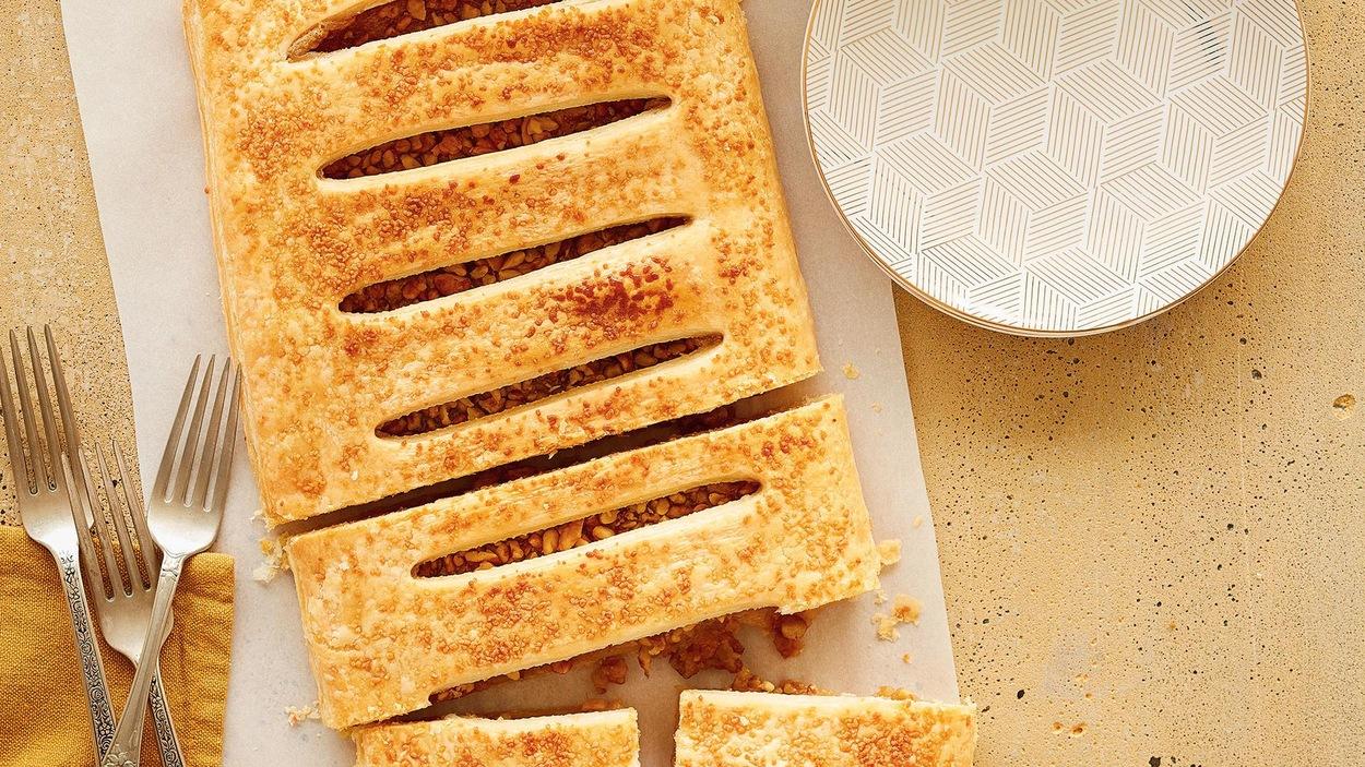 La tarte de style chausson est déposée sur un papier parchemin sur le comptoir.