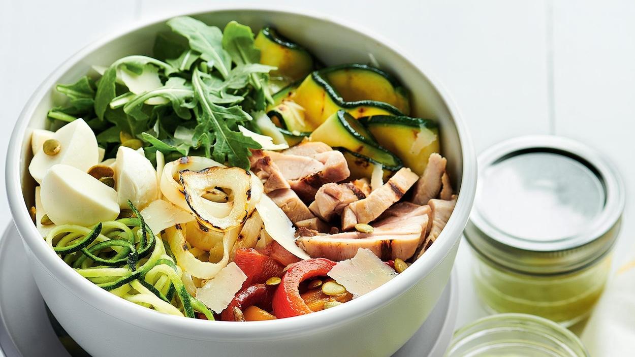 Un bol de légumes et poulet sur une table avec des pots de vinaigrette et un linge jaune et blanc.