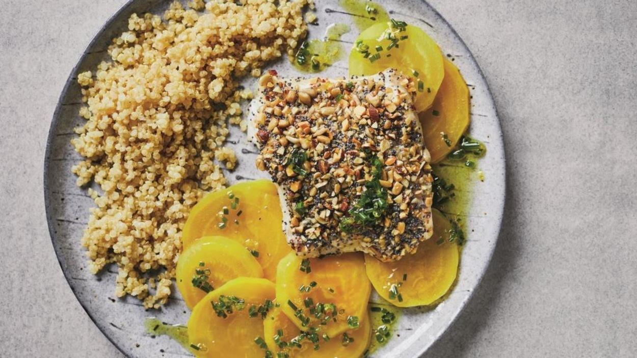 Une assiette avec un poisson en croûte, des betteraves en tranches et du quinoa.