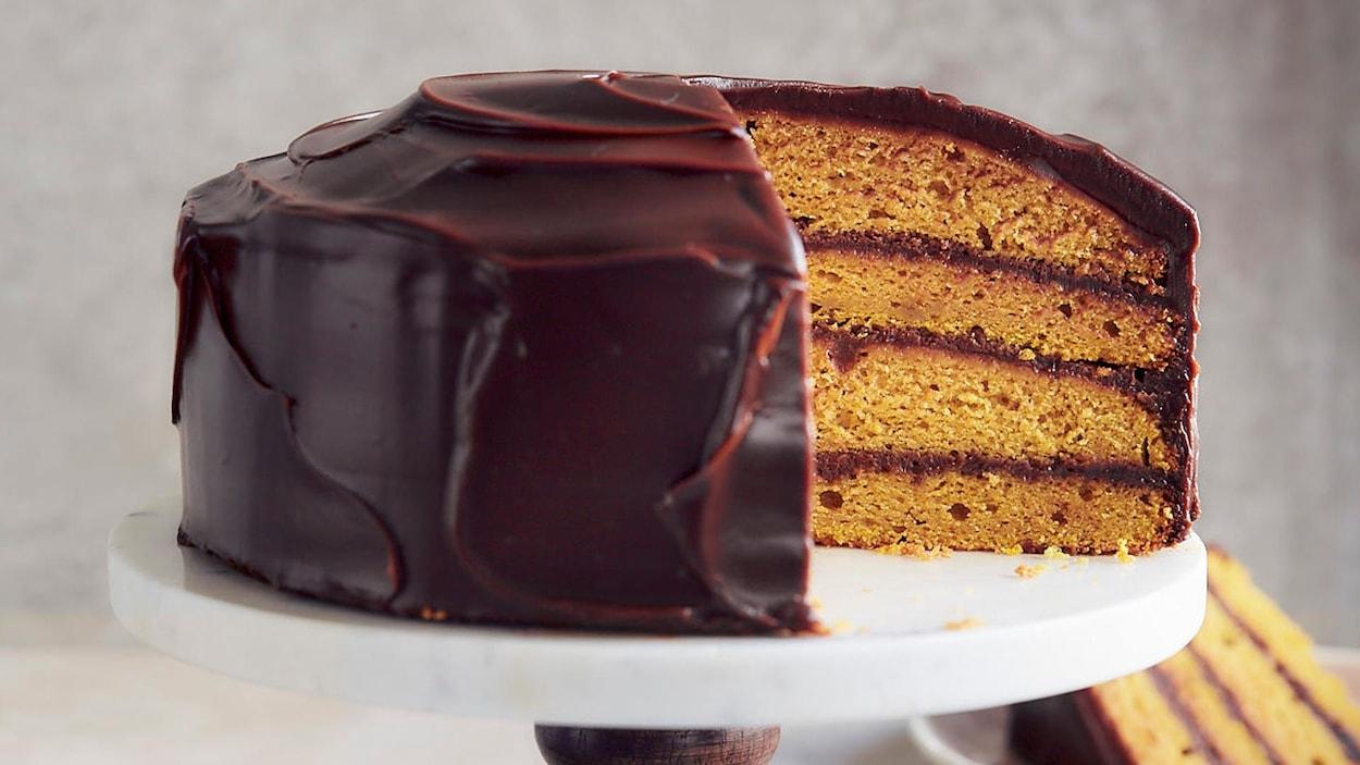 Un gâteau à 4 étages est recouvert de glaçage au chocolat. Un morceau est déposé dans une assiette sur la table.
