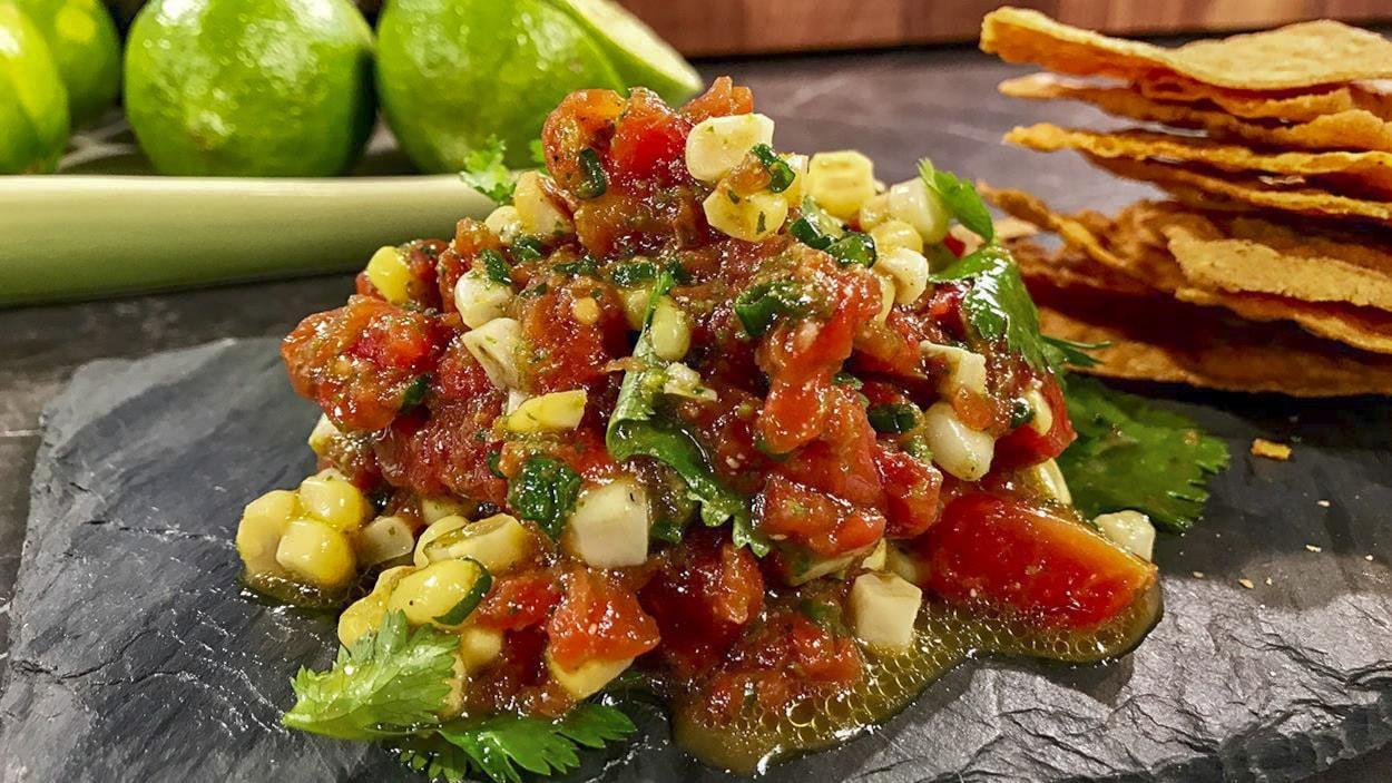 La salsa est composée de tomates, de maïs en grains et d'herbes fraîches