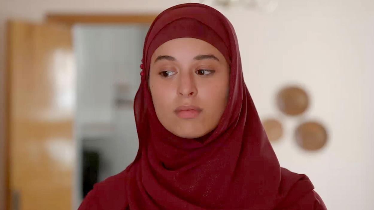 Sassan porte un foulard de couleur bourgogne.