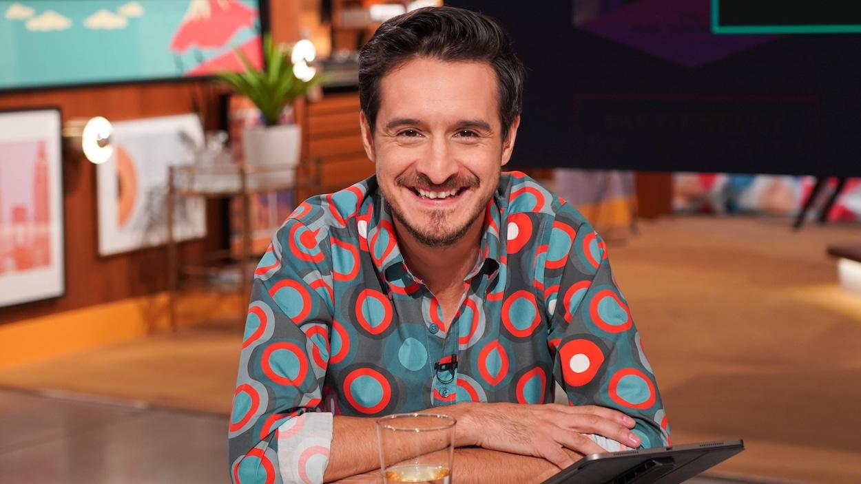 L'animateur souriant porte une chemise colorée