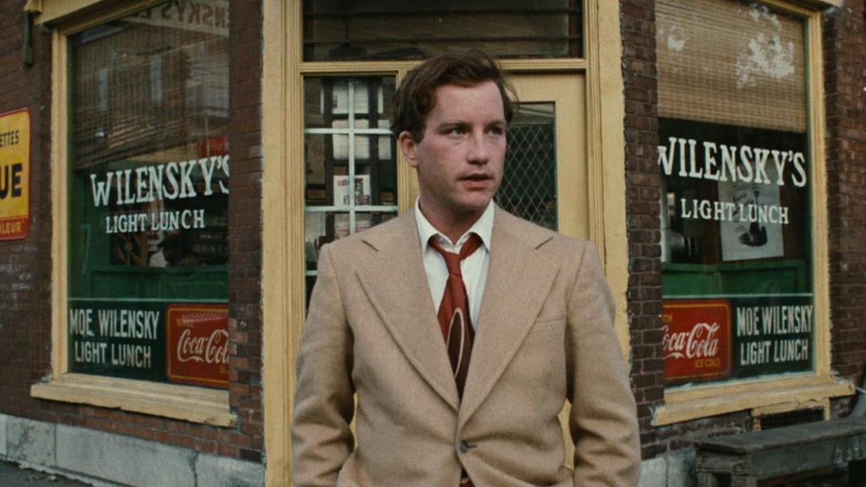 Un homme en costume clair devant la vitrine du restaurant Wilensky's