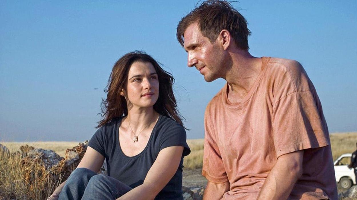 Une femme (Rachel Weisz) et un homme (Ralph Fiennes) assis à l'extérieur, dans une plaine, vêtus de t-shirt et de jeans.