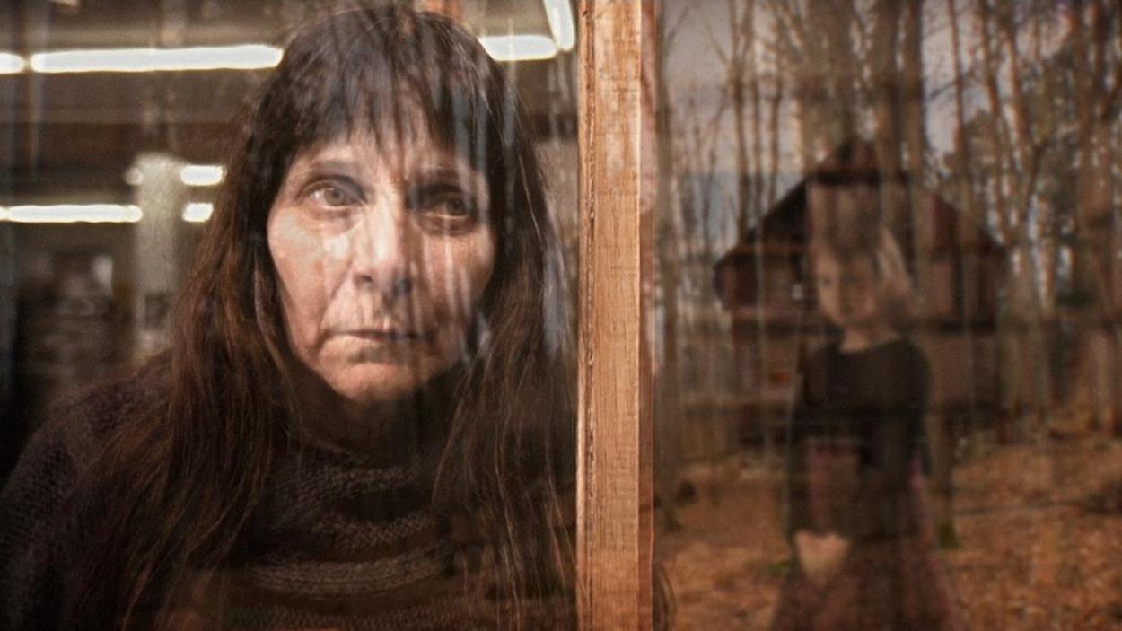 Une femme derrière une fenêtre regarde une petite fille dans la forêt