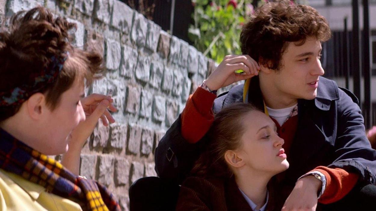 Une jeune fille assise contre un garçon assis en hauteur, dehors, devant un mur de briques.
