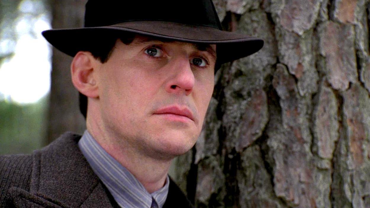 Un homme (Gabriel Byrne) en gros plan, portant un chapeau, à côté d'un arbre.