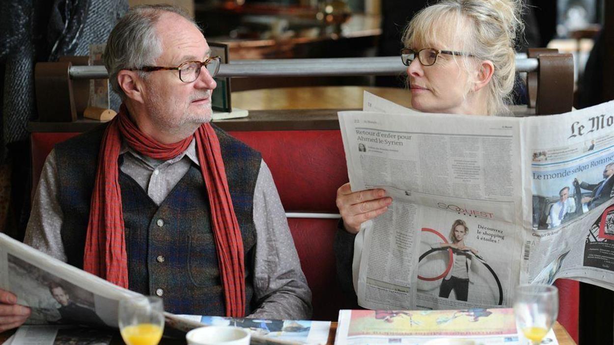Un homme et une femme assis côte à côte dans un café, des journaux dans les mains