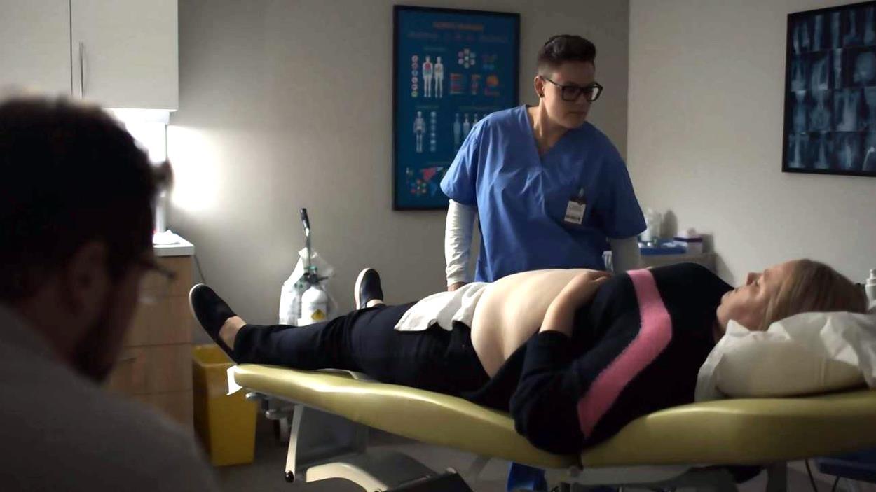 La technologue se tient debout à côté de Caroline, allongée pour son échographie.
