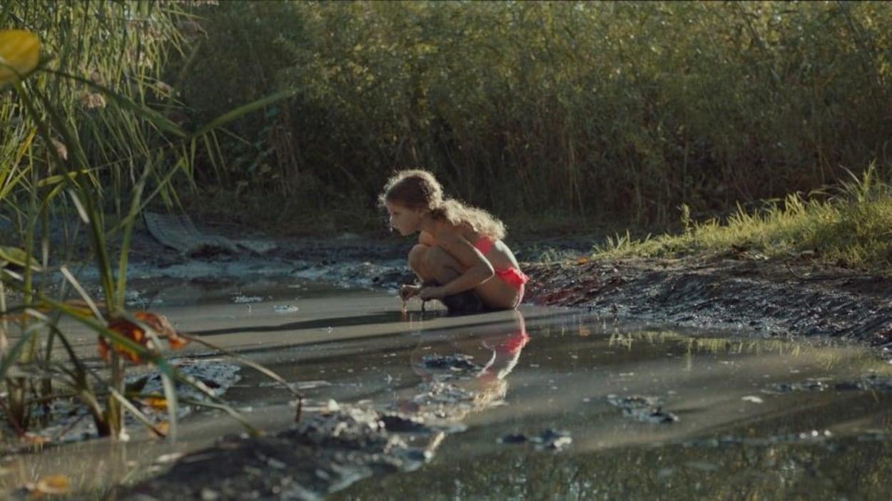 Une petite fille (Irlande Côté) accroupie, en maillot de bain, dans une rivière boueuse.