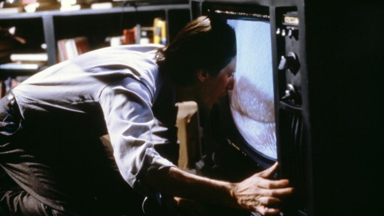 Un homme à genoux commence à entrer dans l'écran de sa télévision qui figure une bouche en gros plan
