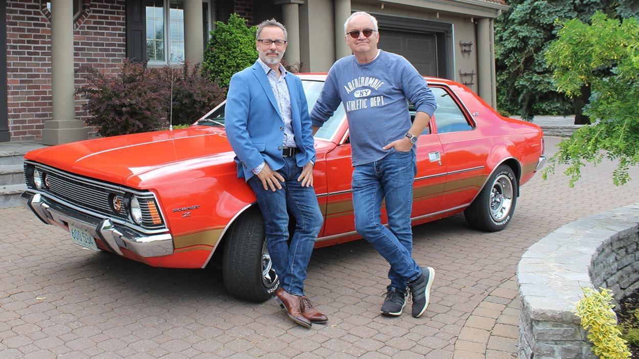 Serge Beauchemin et Michel Barrette devant une voiture rouge.