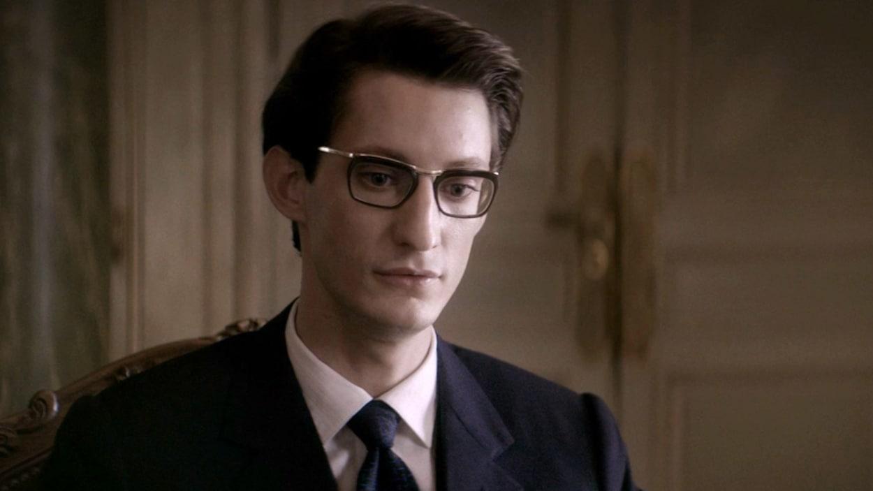 Un homme en costume portant des lunettes.