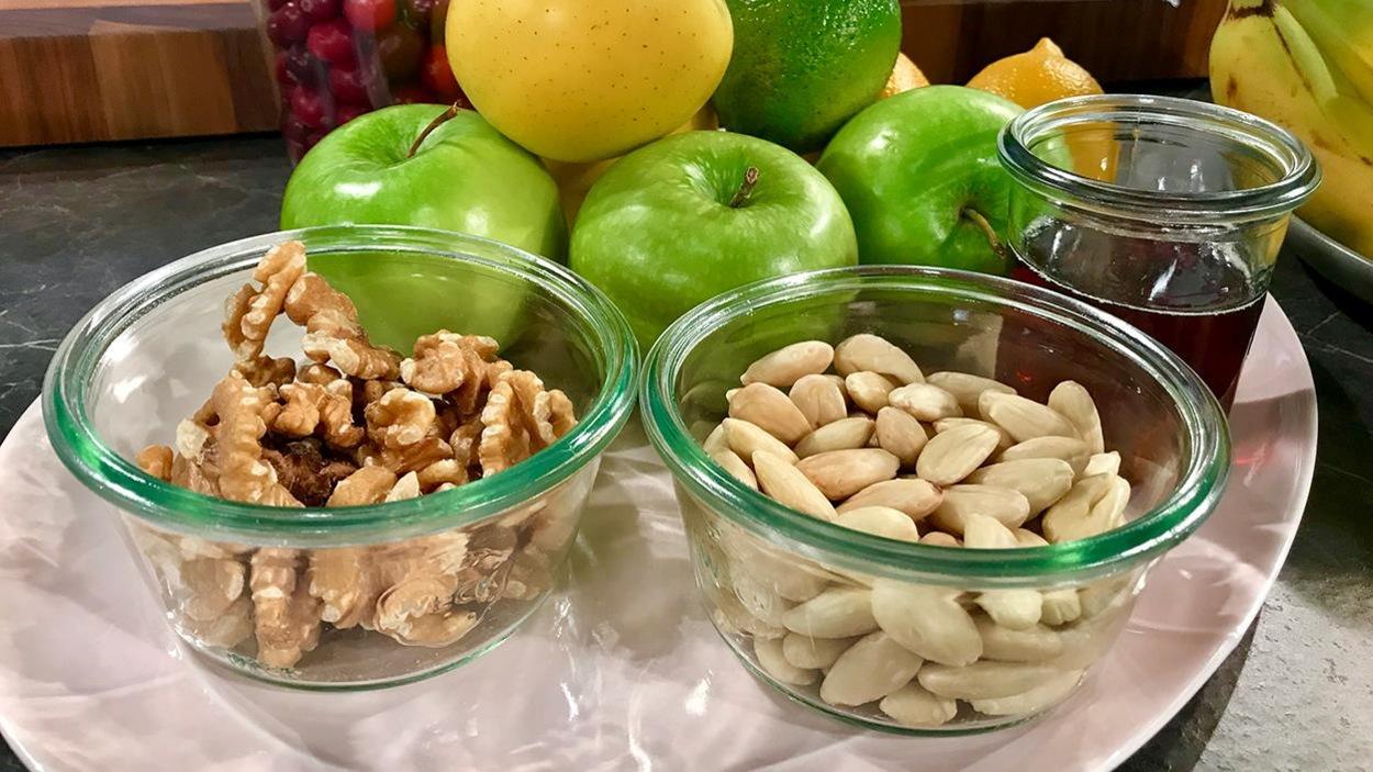 Trois bols en verre contenant avec des amandes, des noix de Grenoble et du sirop d'érable.
