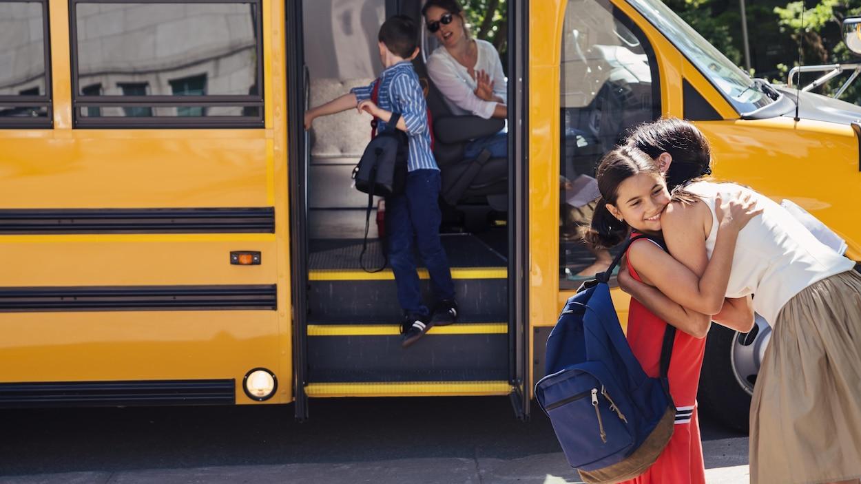 Une femme enlace son enfant devant l'autobus scolaire arrêté devant elles.