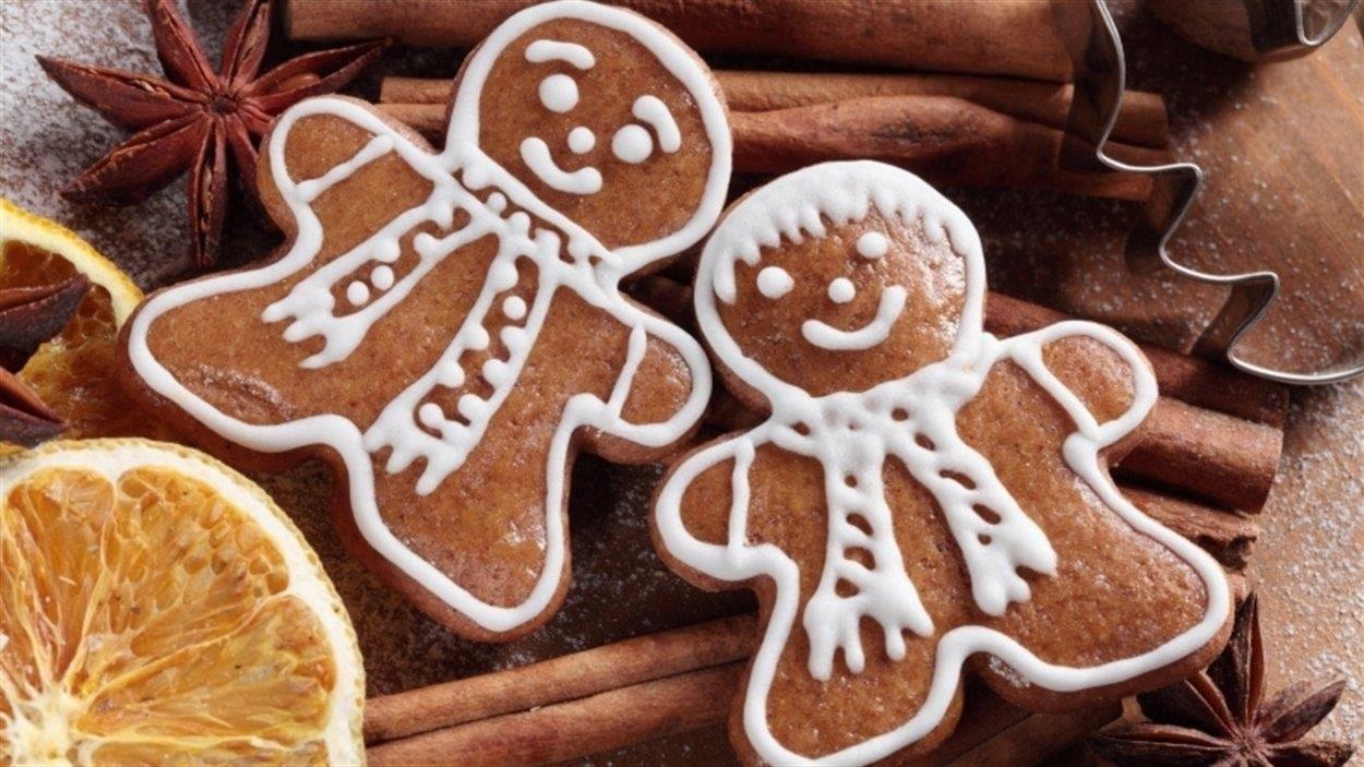 Deux bonhommes de pain d'épices sont décorés avec du glaçage pour faire un visage, des cheveux et un foulard. Les biscuits sont étendus sur des bâtons de cannelle.