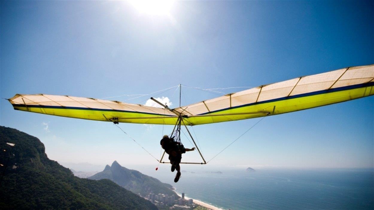 Un pilote de deltaplane s'envole au-dessus d'une colline verdoyante. Au loin on voit la mer.