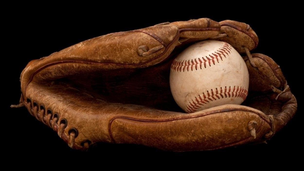 Gros plan sur un gant de receveur au baseball, tenant une balle.