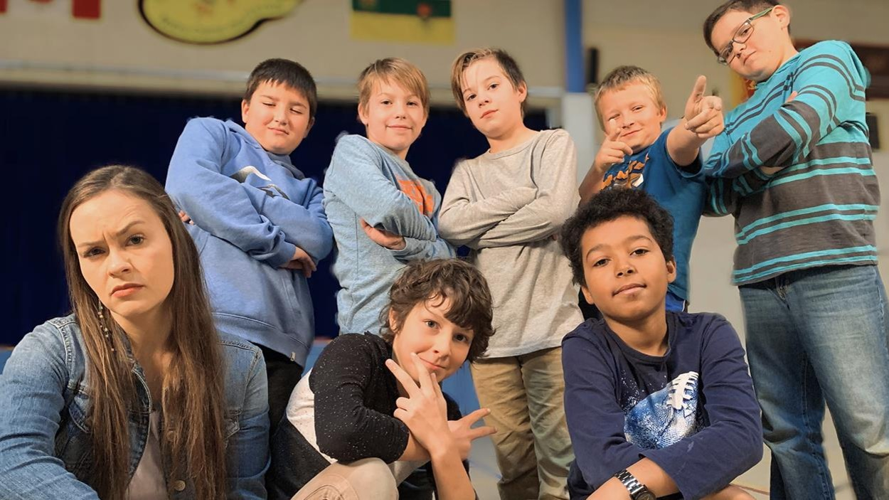 Mélissa est entourée par des jeunes garçons qui prennent chacun une pose cool