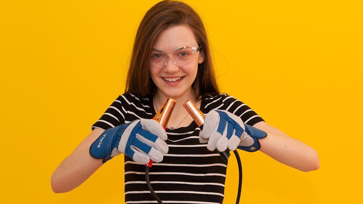 Sur un fond jaune, Jade porte des lunettes de sécurité et des gants de construction. Elle tient dans ses mains des câbles de démarrage.