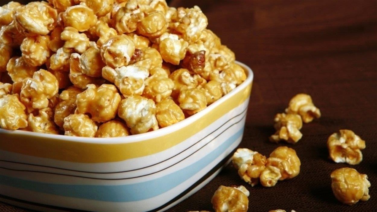 Gros plan sur un bol de pop corn au caramel. Quelques grains éclatés sont tombés sur la table.