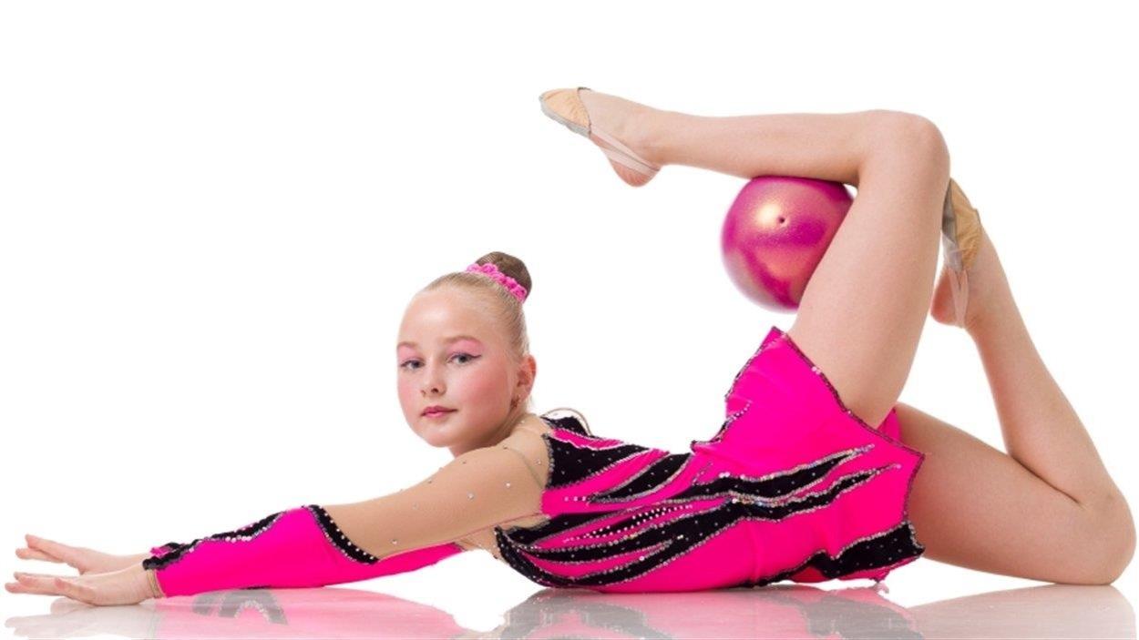 Une jeune gymnaste est sur le ventre, au sol, et manipule un ballon avec ses jambes.