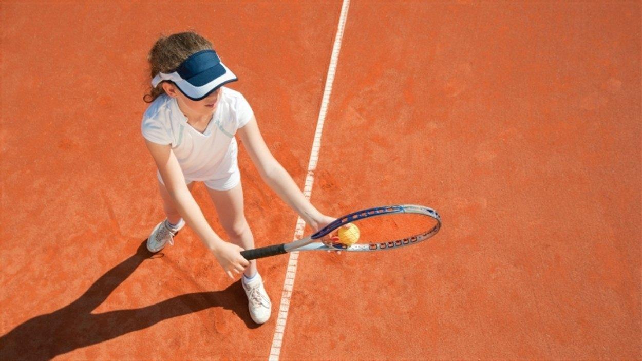Une jeune fille se prépare à faire un service sur un court de tennis.