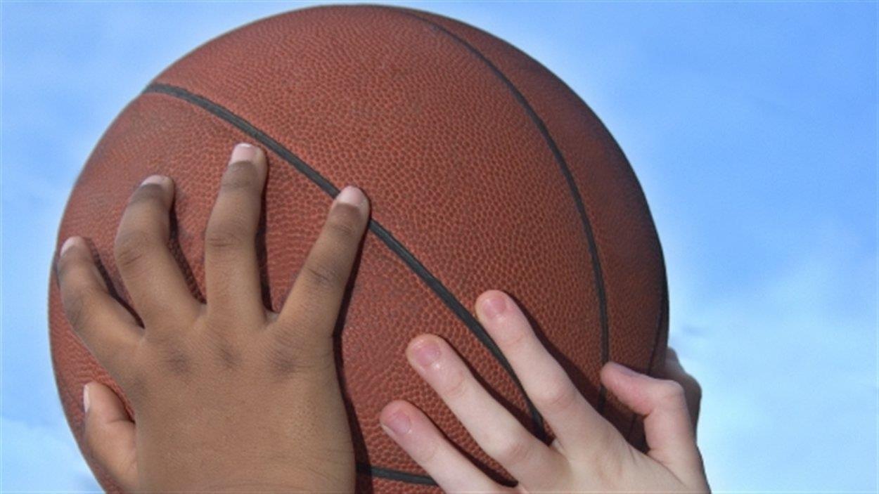 Deux paires de mains tiennent un ballon.