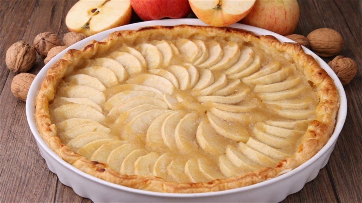 Une tarte aux pommes est déposée sur une table de planches de bois. Des pommes et des noix de Grenoble décorent la table.