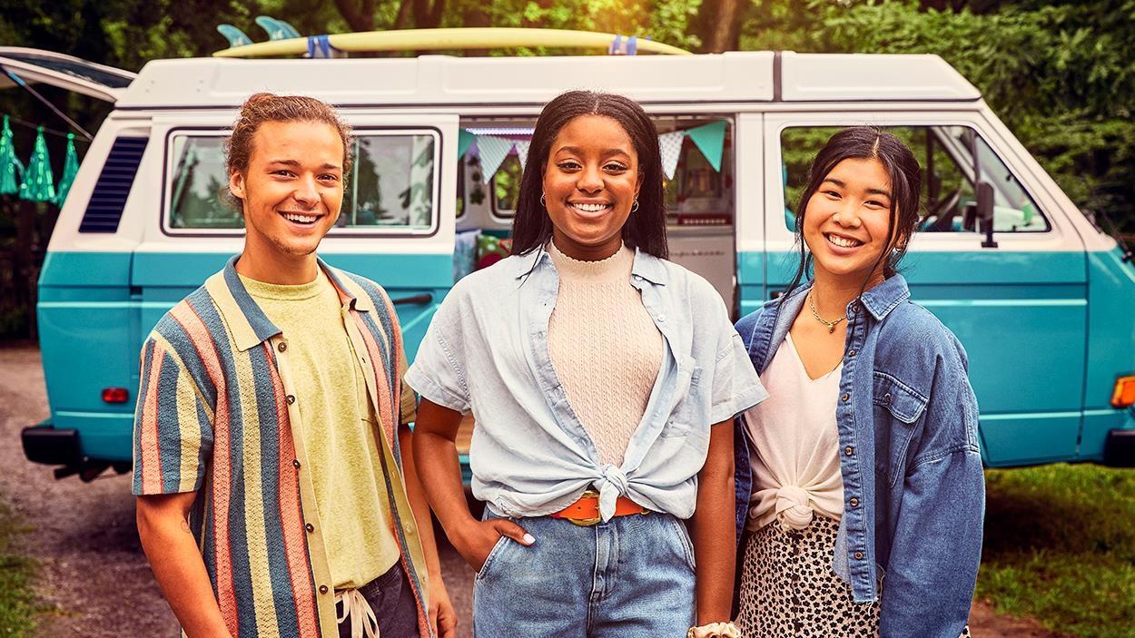 Les trois ados sourient en posant devant leur van