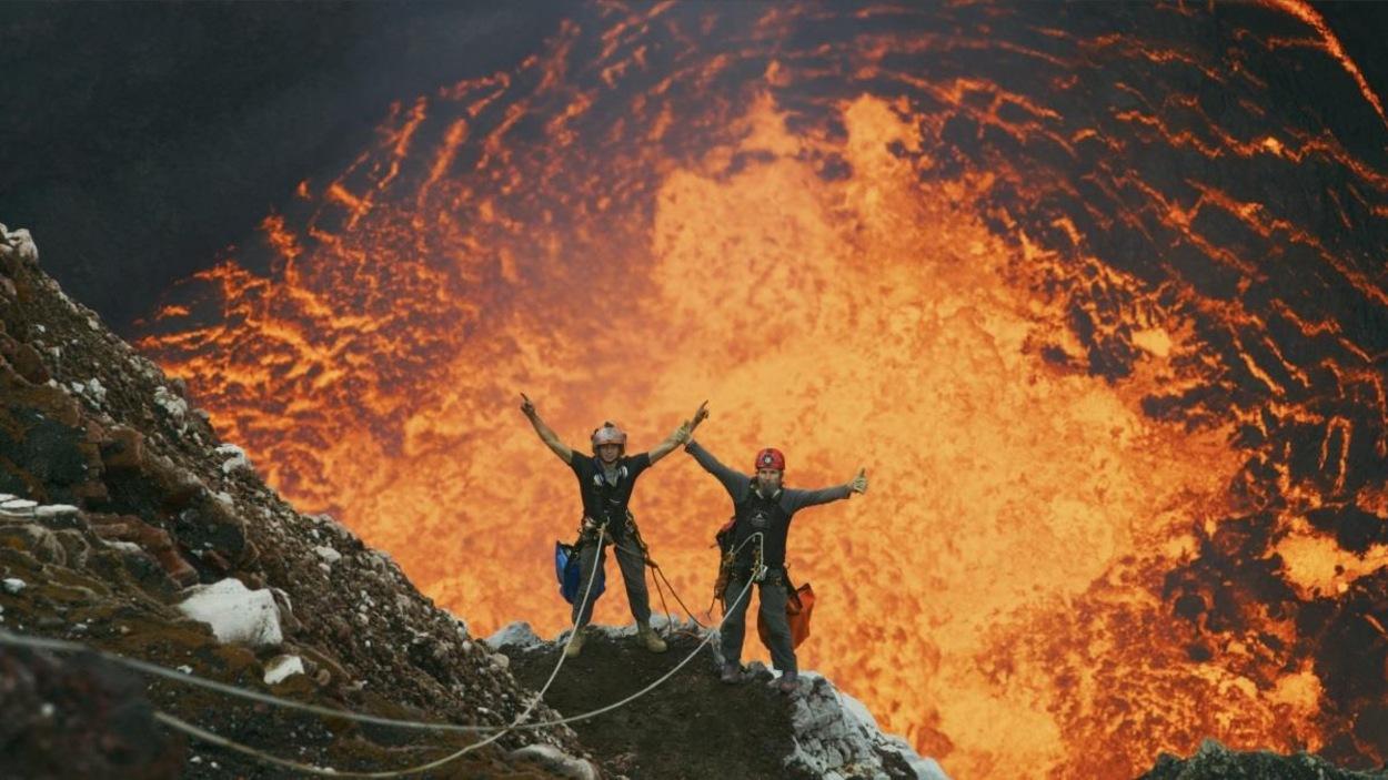 On voit le volcan en éruption et les deux hommes attachés à des cordes.