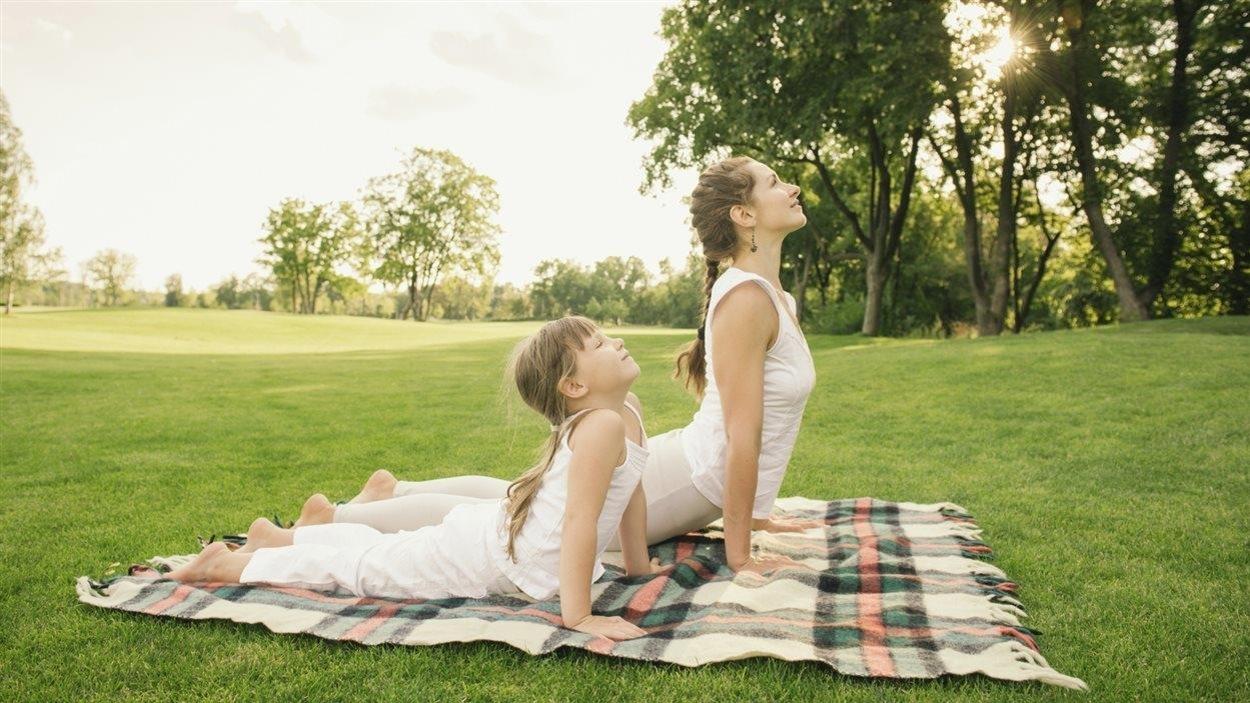 Une mère et sa fille font la position du cobra sur une couverture dans un parc gazonné.