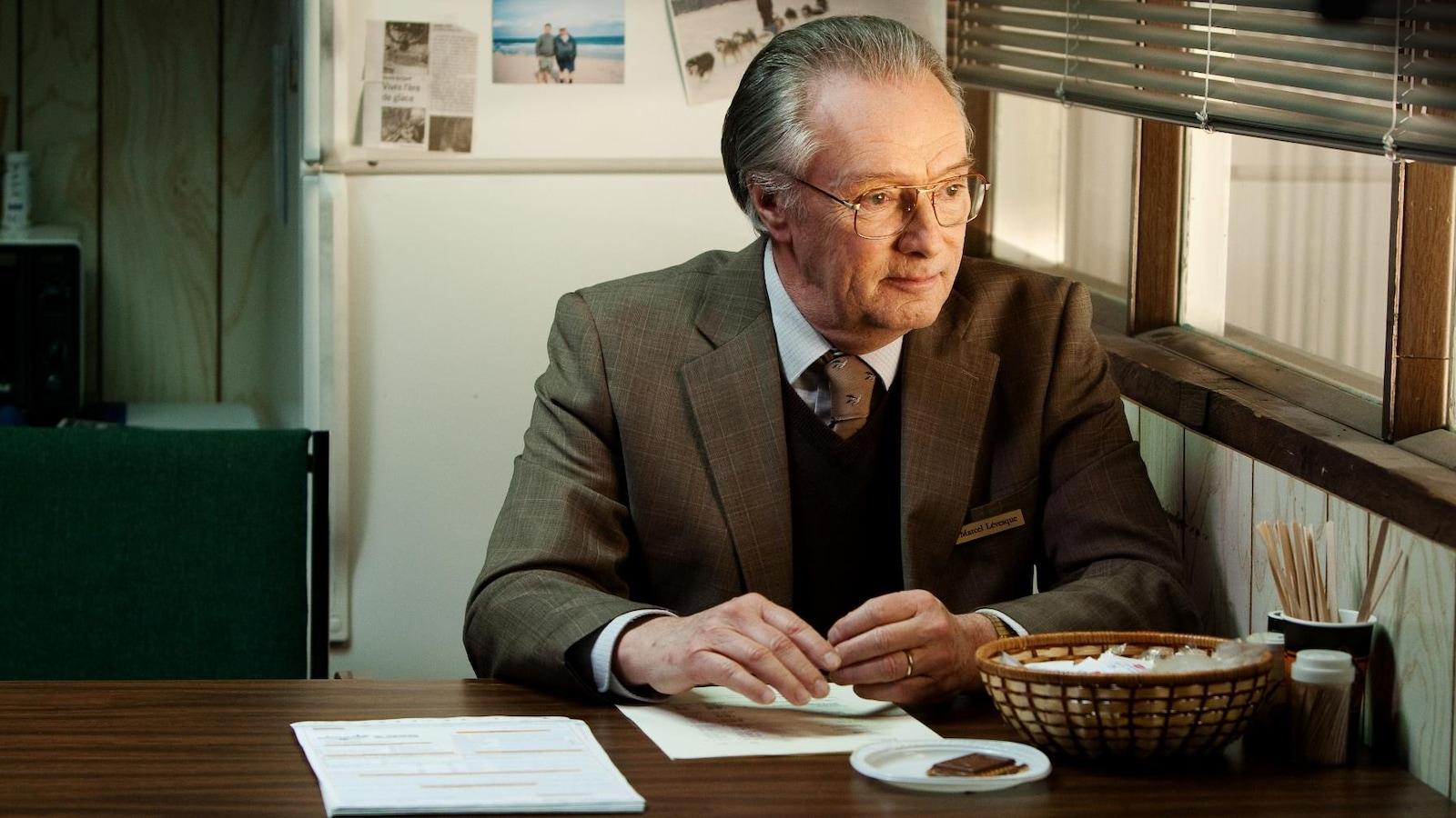Un homme, en costume, assis à la table d'un bureau, regarde par la fenêtre