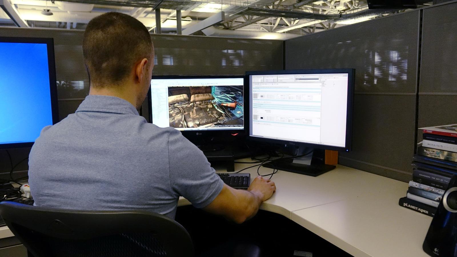 À l'aide du logiciel du moteur de jeu, Michel Lanoie navigue dans une scène d'un secteur du village Golem du jeu Deus Ex : Mankind Divided.